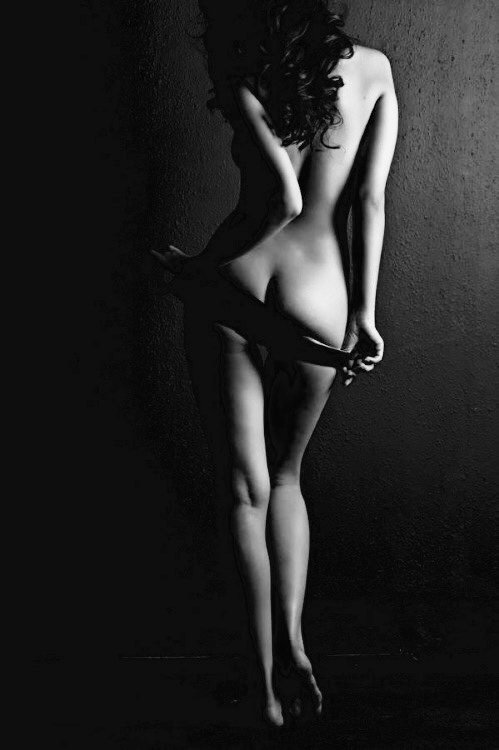 Art nude, perfect naked body, woman on dark background, black and white studio shot stock photo