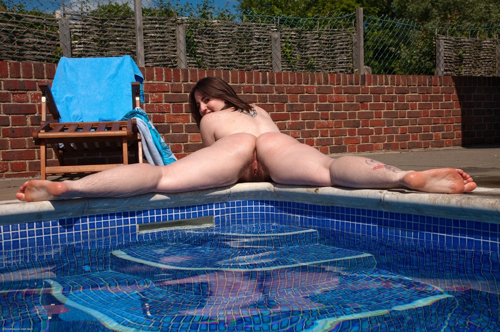 Naked girls swim in the rubber rings in the pool