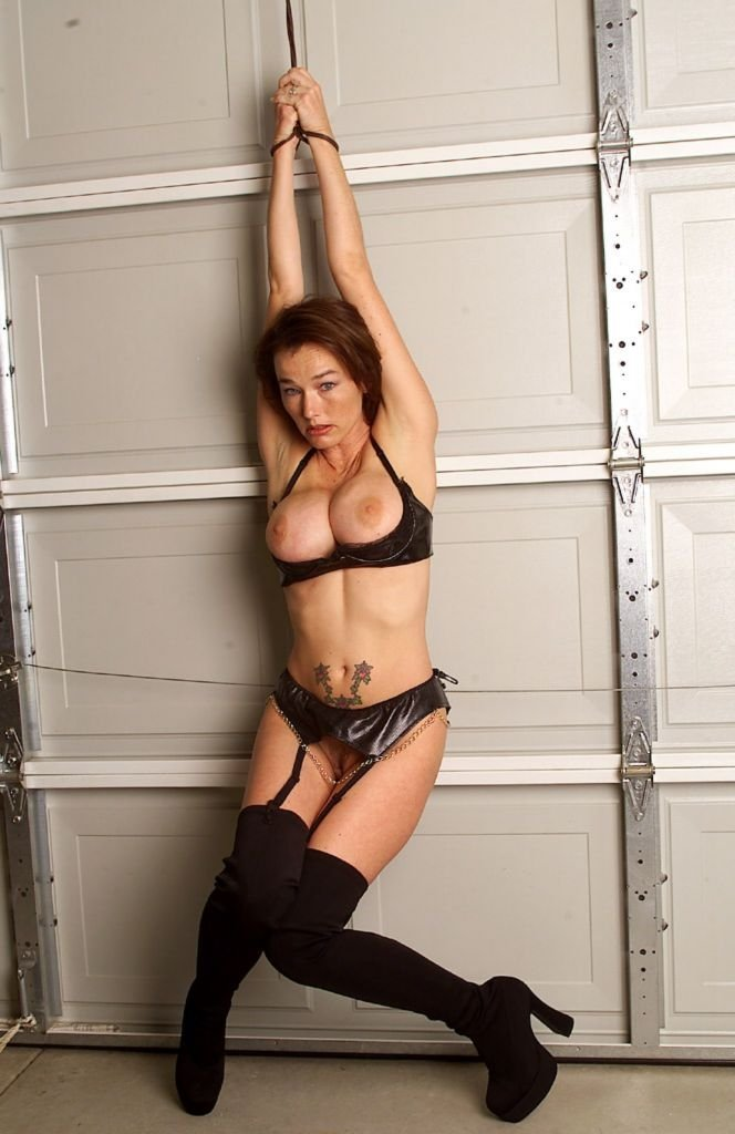 Blonde girlfriend in lingerie with leather whip and handcuffs